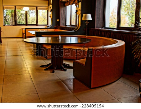 Curved modern bench around a table in an upmarket nightclub, restaurant or bar with windows along the walls