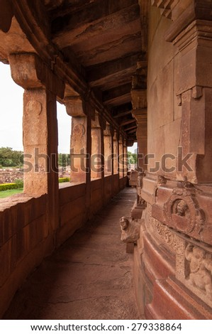 Curved pillared corridor at Durga temple, Aihole, Karnataka. The temple is built using red sandstone.