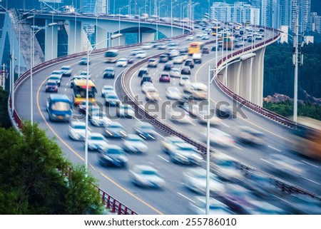 curved ramp bridge with busy traffic vehicles motion blur - stock photo