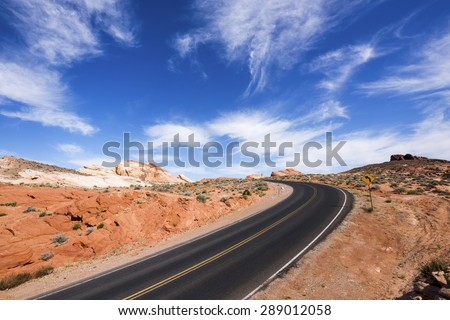 Curved road through rocky desert in Valley of Fire State Park, Nevada. - stock photo
