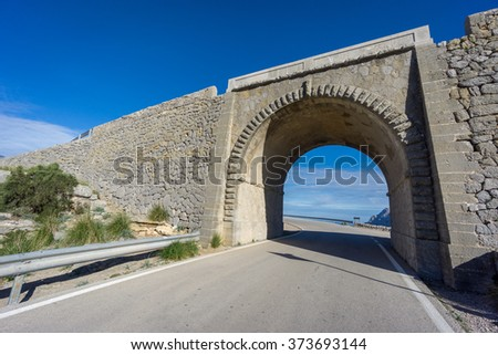 Curved road under bridge - stock photo