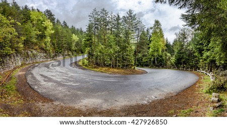 Curved serpentine mountain road in romanian carpathian. Panoramic montage from 3 HDR images - stock photo