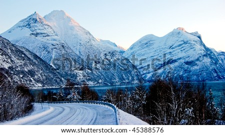 Curved snowy road in Norway, winter