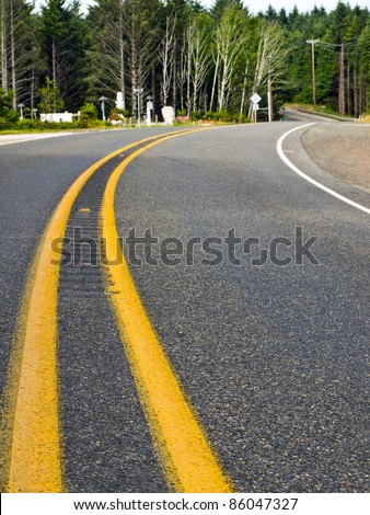 Curved Two Lane Country Road Winding Through a Forest - stock photo