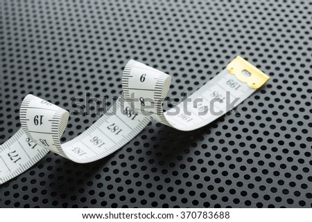 Curved white measuring tape on black background  perforated - stock photo