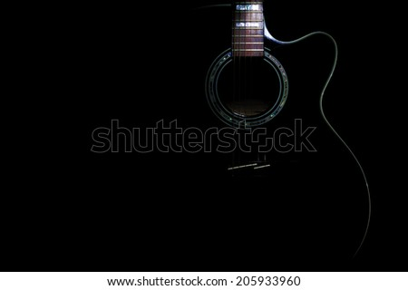 curves of a black body guitar lit - focus on the rosette - stock photo