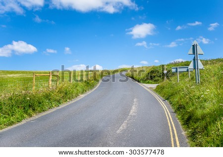 Curving Country Road in Cornwall on Clear Spring Day - stock photo