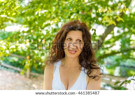 Curvy menopausal woman standing in a park with crossed arms is biting her lip with puzzled look