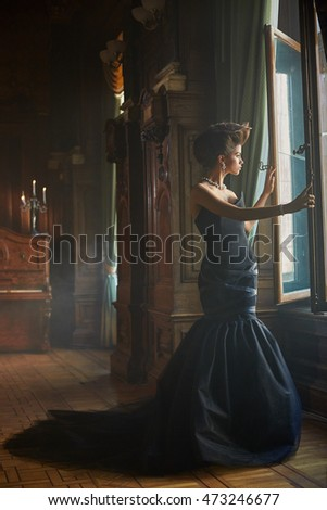Curvy model leans on the open window while standing in old room