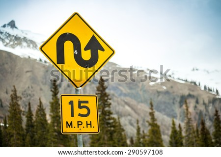 Curvy road sign an 15 m.p.h speed limit - stock photo
