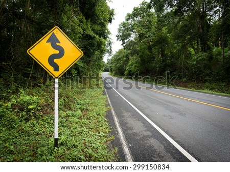 Curvy road sign to the mountain in rural area - stock photo