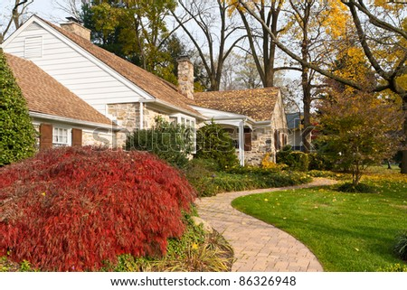 Curvy sidewalk and house in suburban Philadelphia, Pennsylvania, United States in Autumn.  Japanese maple in the left foreground. - stock photo