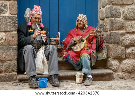CUSCO, PERU, NOVEMBER 26 2011: Two peruvian blind men with traditional clothes playing flute and mandoline in the street of Cusco, Peru - stock photo