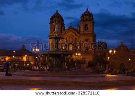 Cusco, Peru - September 2, 2015: People on main square, Plaza de Armas, with facade of church in Cusco, Peru, former Inca capital, famous travel destination in the world. Night view.