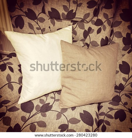 Cushions decorating a sofa with floral design, retro style furniture. - stock photo