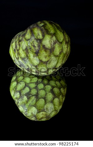 Custard apple, also known as Bullocks or Bulls Heart.On black with reflection.
