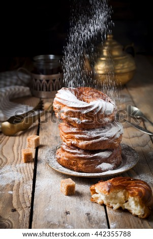 Custard cream ring cakes with curd cream and powdered sugar on a dark wooden background.Selective focus. - stock photo