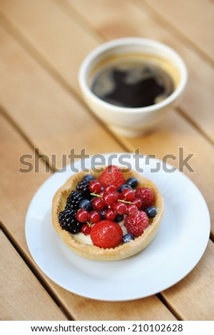 Custard fruit tart and cup of coffee in the outdoors cafe