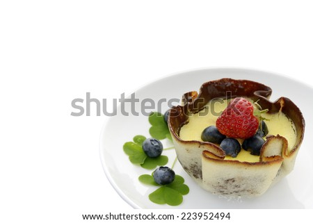 Custard pie decorated with blueberries, strawberry and clover leaves - stock photo