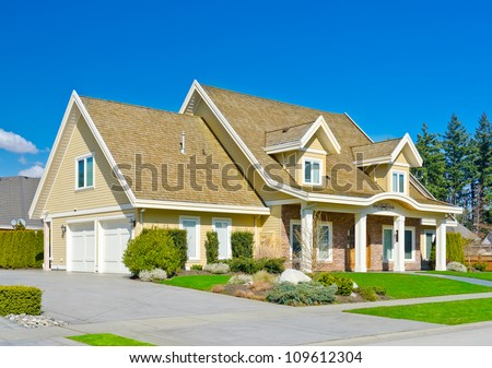 Custom built big luxury house with double doors garage in a residential neighborhood. Suburbs of Vancouver ( Surrey ) Canada. - stock photo