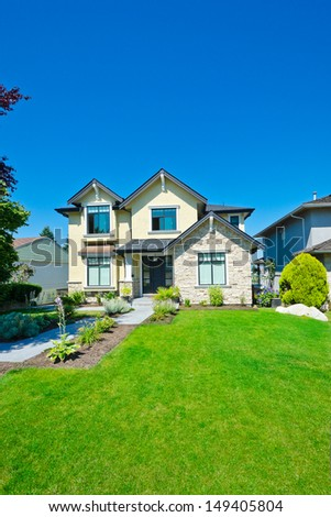 Custom built big luxury house with nicely trimmed front yard, lawn in a residential neighborhood. Vancouver Canada. - stock photo