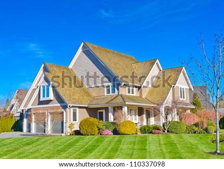 Custom built big luxury house with triple doors garage in a residential neighborhood. Suburbs of Vancouver ( Surrey ) Canada. - stock photo