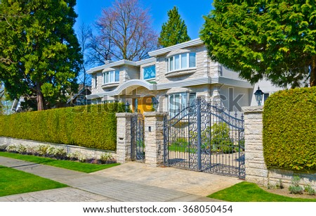 Custom built house behind the gates and with nicely trimmed and landscaped front yard, lawn in a residential neighborhood. Vancouver Canada. - stock photo