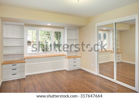 Custom built in shelf ideas office. Bright empty room with hardwood floor and built-in wall shelves - stock photo