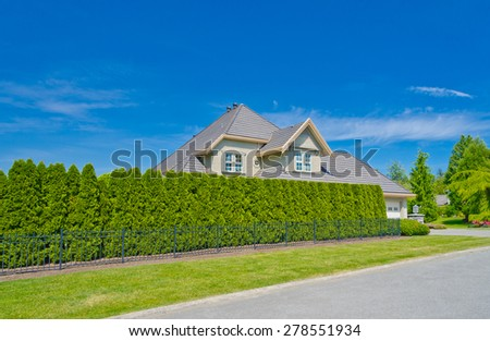 Custom built luxury house behind green fence with nicely trimmed and decorated front yard, lawn in a residential neighborhood. Vancouver Canada.