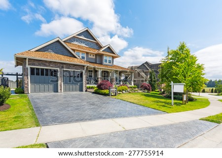 Custom built luxury house for sale with nicely trimmed and designed front yard, lawn in a residential neighborhood in Canada. For sale sign in front of the house by real estate agency.  - stock photo