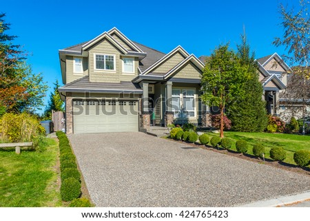 Custom built luxury house, townhouse with nicely trimmed and landscaped front yard, lawn and driveway to garage in a residential neighborhood. Vancouver Canada.