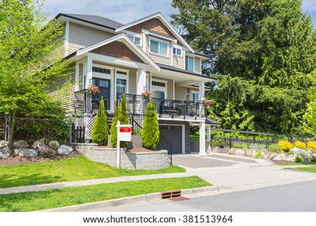 Custom built luxury house with nicely trimmed and designed front yard, lawn in a residential neighbourhood in Canada. House for sale  - stock photo