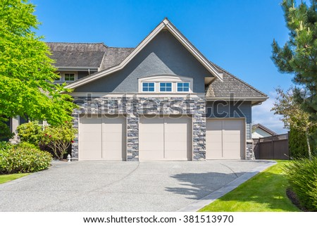 Custom built luxury house with nicely trimmed and designed front yard, lawn in a residential neighbourhood in Canada. Garage doors.  - stock photo