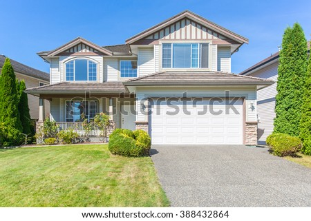 Custom built luxury house with nicely trimmed and designed front yard, lawn in a residential neighbourhood. - stock photo