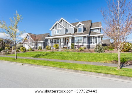 Custom built luxury house with nicely trimmed and designed front yard, lawn in a residential neighbourhood in Canada.