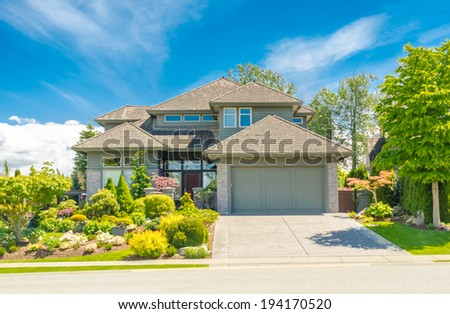 Custom built luxury house with nicely trimmed and landscaped front yard and driveway to double doors garage in residential neigborhood. Vancouver, Canada.