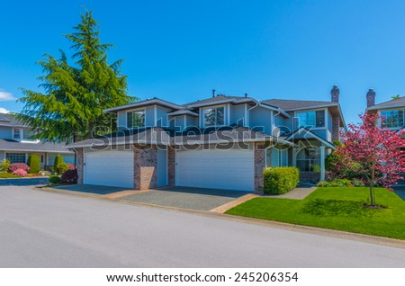 Custom built luxury house with nicely trimmed and landscaped front yard lawn and double doors garage in a residential neighborhood. Vancouver Canada. - stock photo