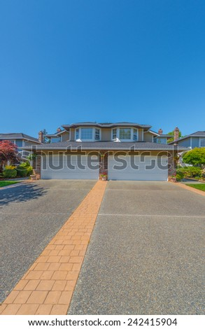 Custom built luxury house with nicely trimmed and landscaped front yard lawn and driveway to garage in a residential neighborhood. Vancouver Canada. Vertical. - stock photo