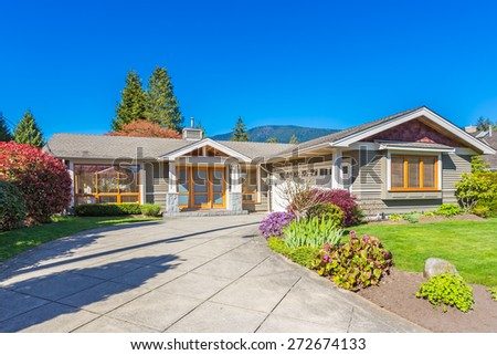 Custom built luxury house with nicely trimmed and landscaped front yard lawn and driveway to garage in a residential neighborhood. Vancouver Canada.