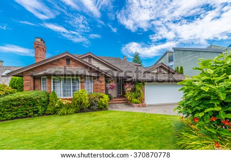 Custom built luxury house with nicely trimmed and landscaped front yard, lawn in a residential neighborhood. Vancouver Canada. - stock photo