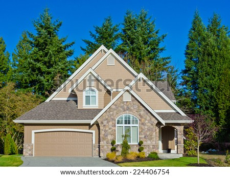 Custom built luxury house with nicely trimmed front yard and driveway to garage lawn in a residential neighborhood. Vancouver Canada. - stock photo