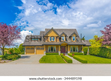 Custom built luxury house with nicely trimmed front yard, lawn and double doors garage with wide long driveway  in a residential neighborhood. Vancouver, Canada. - stock photo