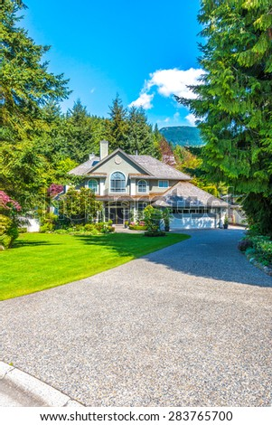 Custom built luxury house with nicely trimmed front yard, lawn and driveway to garage in a residential neighborhood. Vancouver. Canada. Vertical. - stock photo