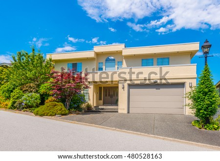 Custom built luxury house with nicely trimmed front yard, lawn and garage in a residential neighborhood. Vancouver Canada.