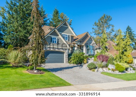 Custom built luxury house with nicely trimmed front yard, lawn and long doorway and driveway in a residential neighborhood. Vancouver Canada. - stock photo