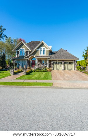 Custom built luxury house with nicely trimmed front yard, lawn and long doorway and driveway in a residential neighborhood. Vancouver Canada. Vertical.