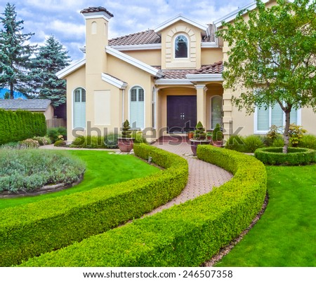 Custom built luxury house with nicely trimmed front yard, lawn and long doorway in a residential neighborhood. Vancouver Canada. - stock photo