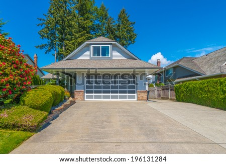 Custom built luxury house with nicely trimmed front yard, lawn and long driveway to the garage in a residential neighborhood. Vancouver, Canada.