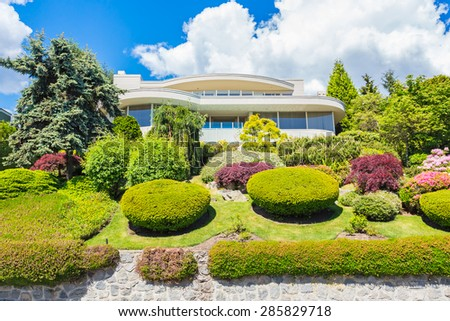 Custom built luxury modern house with nicely trimmed and landscaped front yard lawn and driveway to garage in a residential neighborhood.  - stock photo