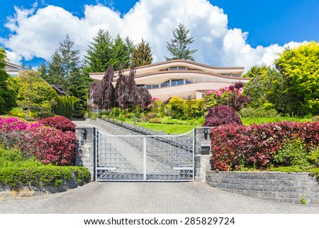 Custom built luxury modern house with nicely trimmed and landscaped front yard lawn and gated driveway in a residential neighborhood.  - stock photo